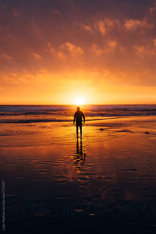A Young Man Stands On The Shore As The Orange Glowing Sun Sets Over The Pacific Ocean by Luke Mattson for Stocksy United