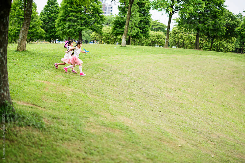 Side view of two children in pink running along park grass by Lawren Lu for Stocksy United