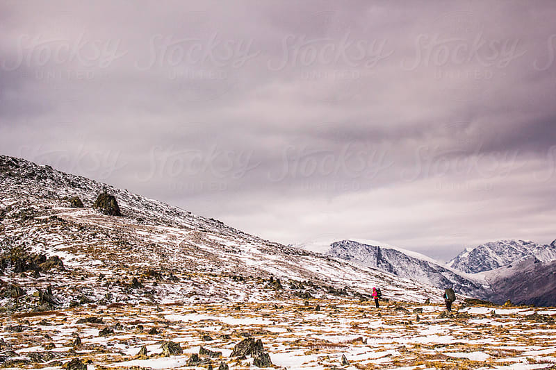 Scenic view of rocky snowed valley and two travellers by Danil Nevsky for Stocksy United