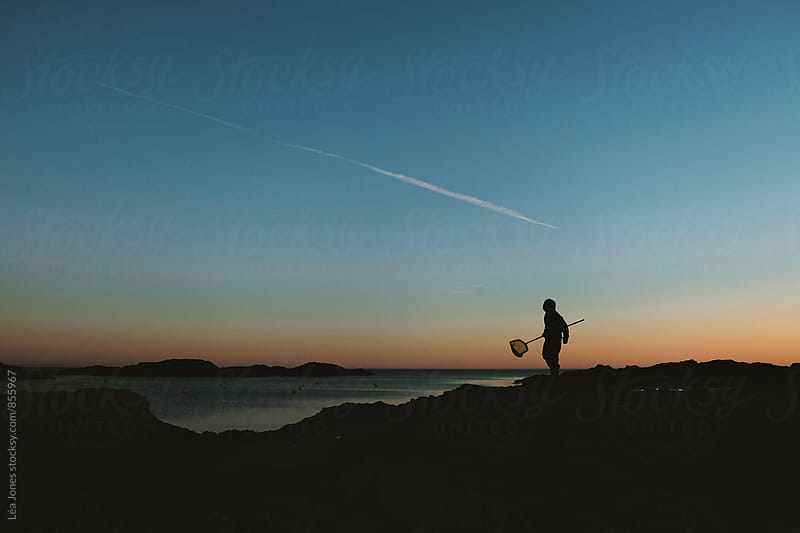 Kid holding a fishing net but he sea at sunset by Léa Jones for Stocksy United