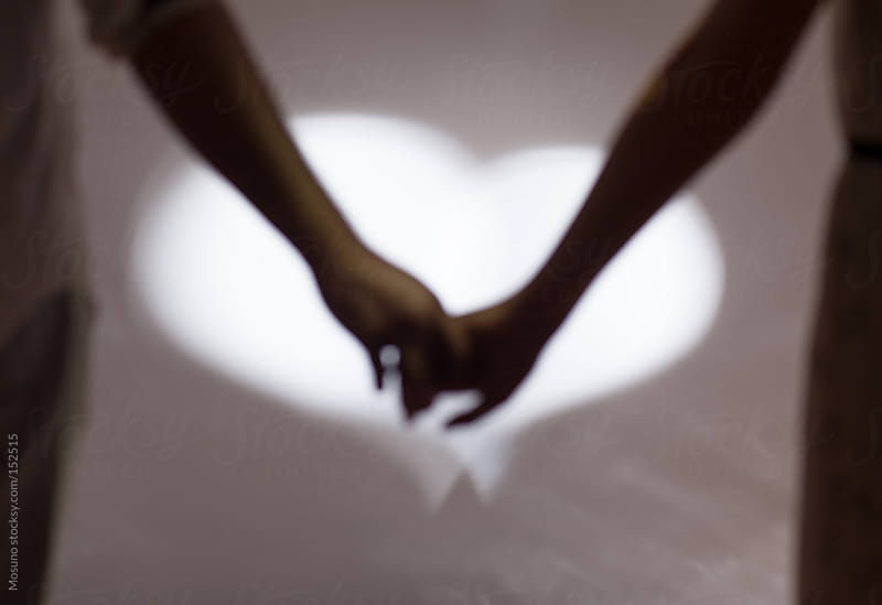 Hands of a Couple Lit by Heart Shaped Light by Mosuno for Stocksy United