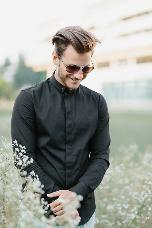 Cute man in sunglasses walking among wildflowers by Amir Kaljikovic for Stocksy United