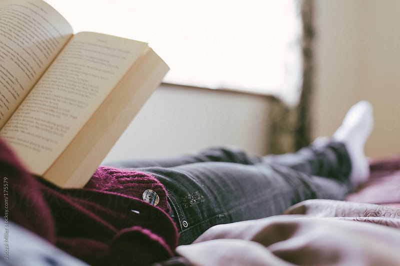 Girl, relaxing on a bed, reading a book by Jacqui Miller for Stocksy United