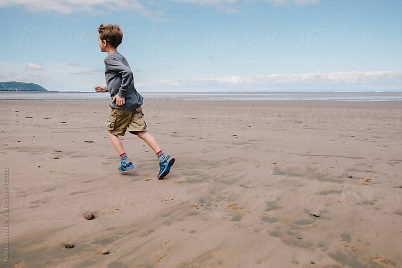 Child running on wet sand by Rebecca Spencer for Stocksy United