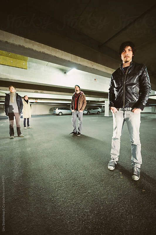 Lifesyle shot of four genuine men standing in urban parking garage by Urs Siedentop & Co for Stocksy United