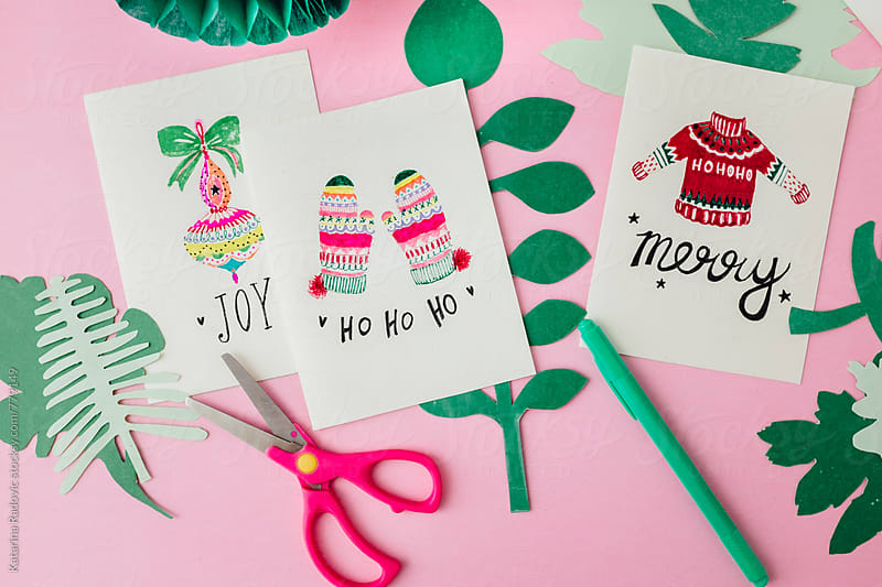 Hand Painted Christmas Cards on a Pink Background with Green Leaves Decoration by Katarina Radovic for Stocksy United