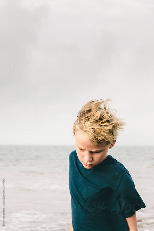 Boy with Windswept Hair by the Sea by Stephen Morris for Stocksy United