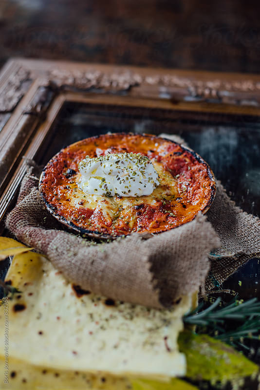 Lasagna meal in the rustic plate on wooden frame by Boris Jovanovic for Stocksy United