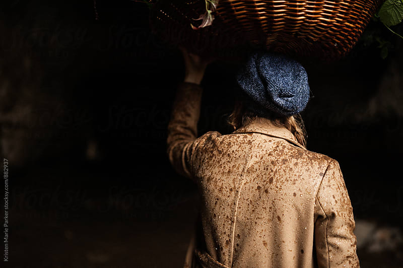 Woman with wicker basket on head covered in rain drops by Kristen Marie Parker for Stocksy United