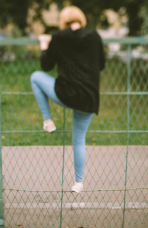 teen girl climbing over the fence by Alexey Kuzma for Stocksy United