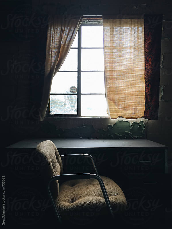 Abandoned office space, desk and chairs, with sunlight shining through a window with drapes by Greg Schmigel for Stocksy United
