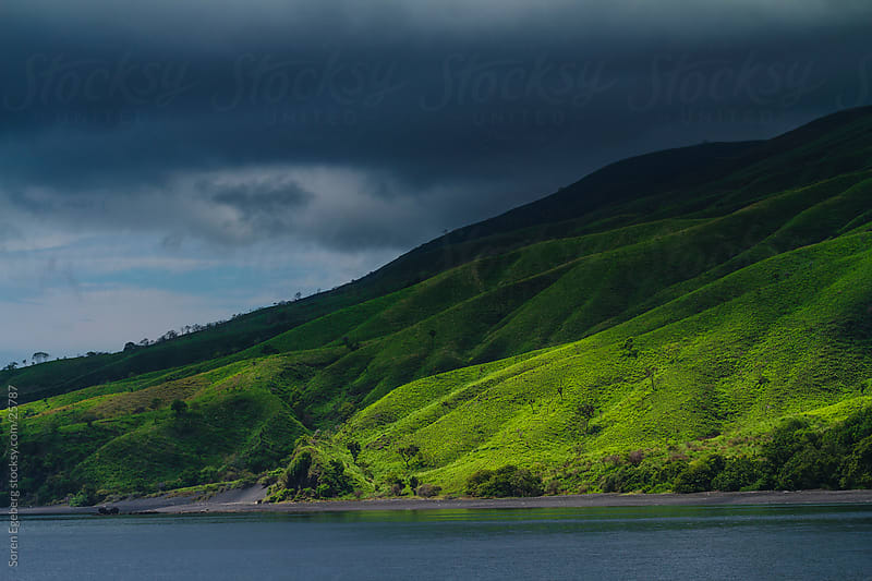 Lush green tropical island with dark clouds in Indonesia by Soren Egeberg for Stocksy United