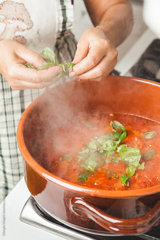 Adding Basil to the Hot Pot of Tomato Soup by Giorgio Magini for Stocksy United