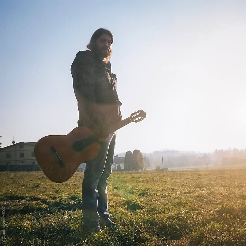 Guitarist holding a guitar in the field by GIC for Stocksy United