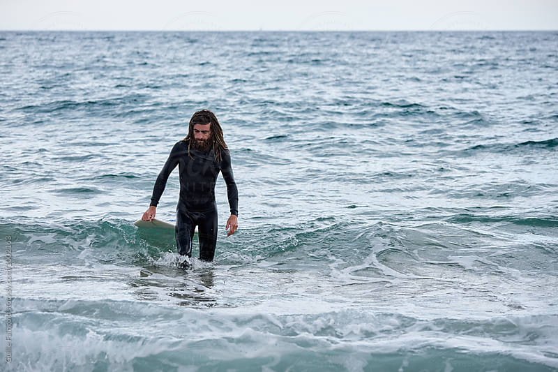 Surfer walking in water with board by Guille Faingold for Stocksy United