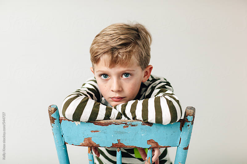 portrait of a bored little boy by Kelly Knox for Stocksy United