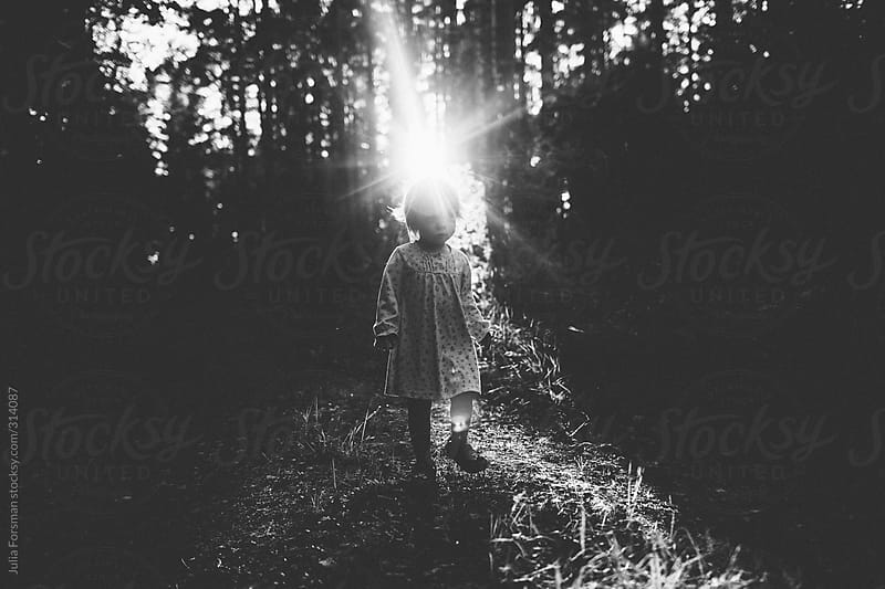 Fairy-like girl in forest with sun flare by Julia Forsman for Stocksy United