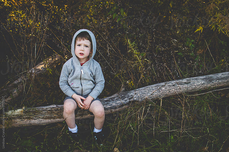 Boy sitting on a log by Lindsay Crandall for Stocksy United