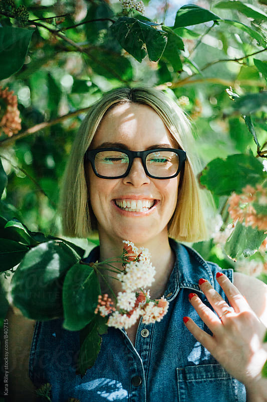 Blonde Woman with glasses amongst flowers laughing by Kara Riley for Stocksy United
