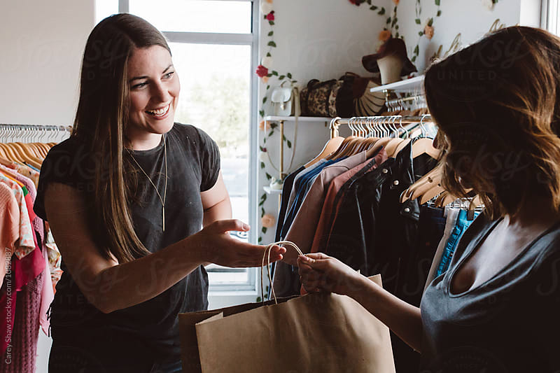 Clothing store owner helping customer with purchase by Carey Shaw for Stocksy United