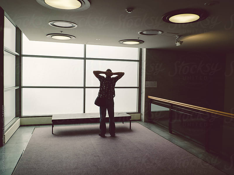 Man in an Office Building, stretching. by Gary Radler Photography for Stocksy United