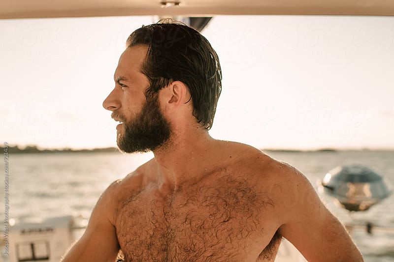 A shirtless man on a sailboat by Joseph West Photography for Stocksy United