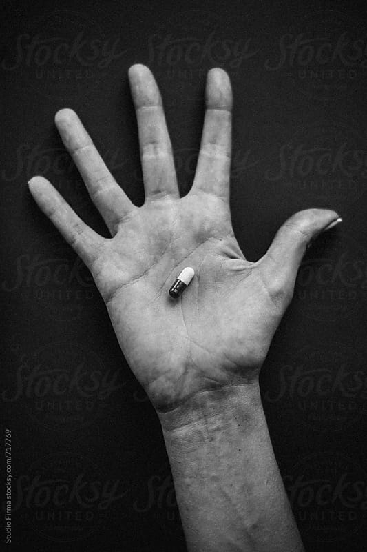 Hand of a young Woman holding a pill. by Studio Firma for Stocksy United