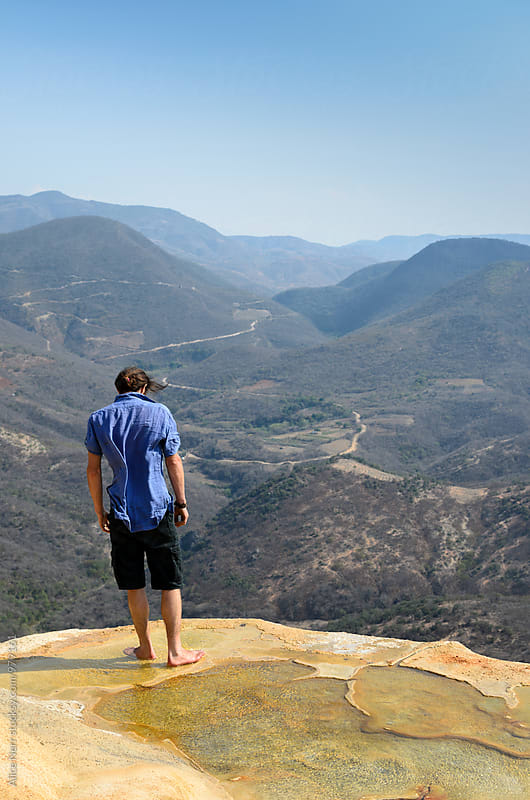 Man standing in a natural pool at the edge of a mountain by Alice Nerr for Stocksy United