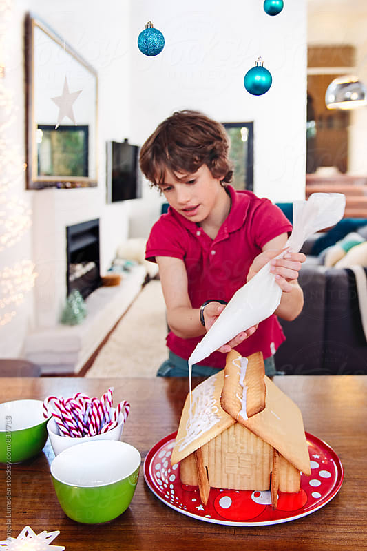 Child decorating a home-made ginger bread house at christmas by Angela Lumsden for Stocksy United