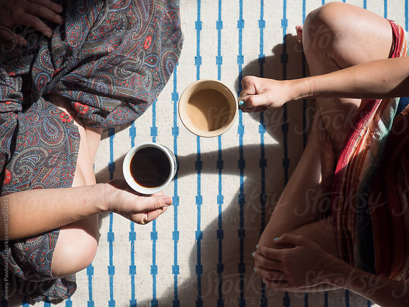 Overhead shot of two women drinking coffee on floor by Jeremy Pawlowski for Stocksy United