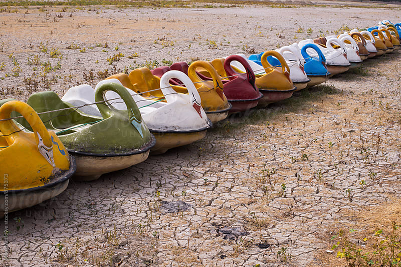 Line of paddle boats on a dried out river bed by Mike Marlowe for Stocksy United
