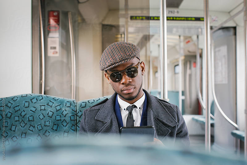 Portrait of Fashionable Black Businessman Reading Ebook in Train by Julien L. Balmer for Stocksy United