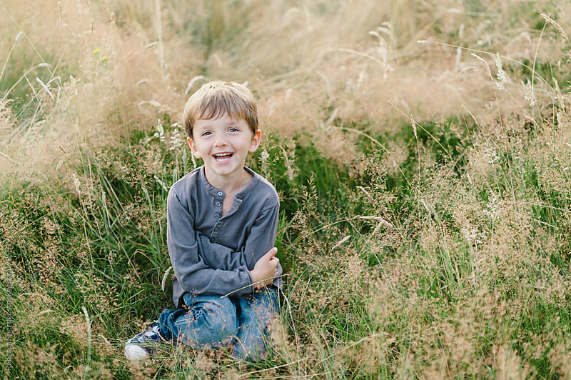 Cute child sits cross legged in a summer meadow by Rebecca Spencer for Stocksy United