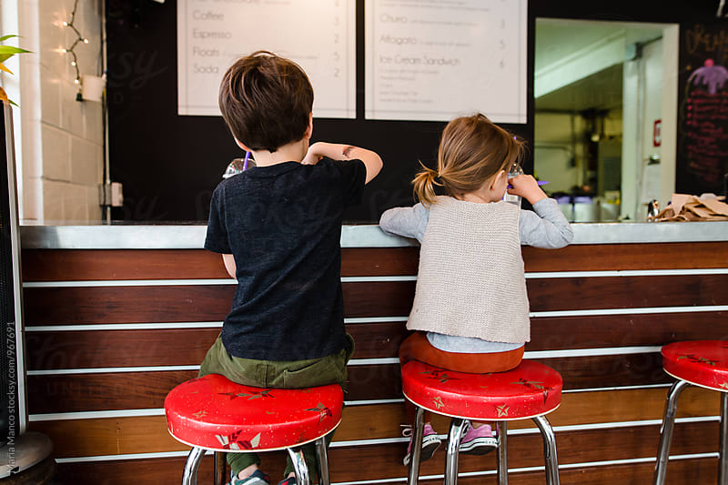 children sit on vintage stools in diner by Maria Manco for Stocksy United