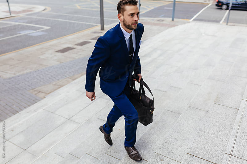 Businessman walking in the city by HEX. for Stocksy United