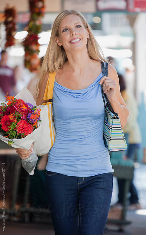 Smiling woman with bag and bouquet by Andersen Ross Photography for Stocksy United