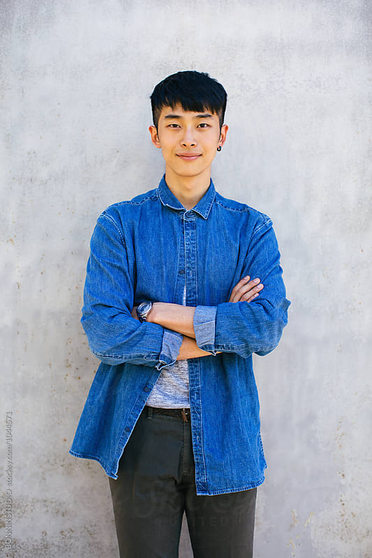 Portrait of a stylish young asian man standing outside.  by BONNINSTUDIO for Stocksy United