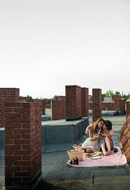 Young women having a picnic on a rooftop by VegterFoto for Stocksy United