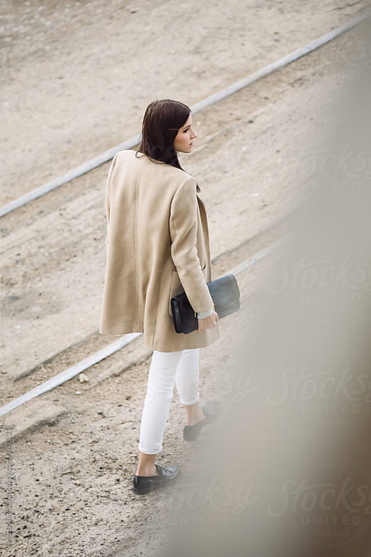 A woman walking away along the tracks by Ania Boniecka for Stocksy United