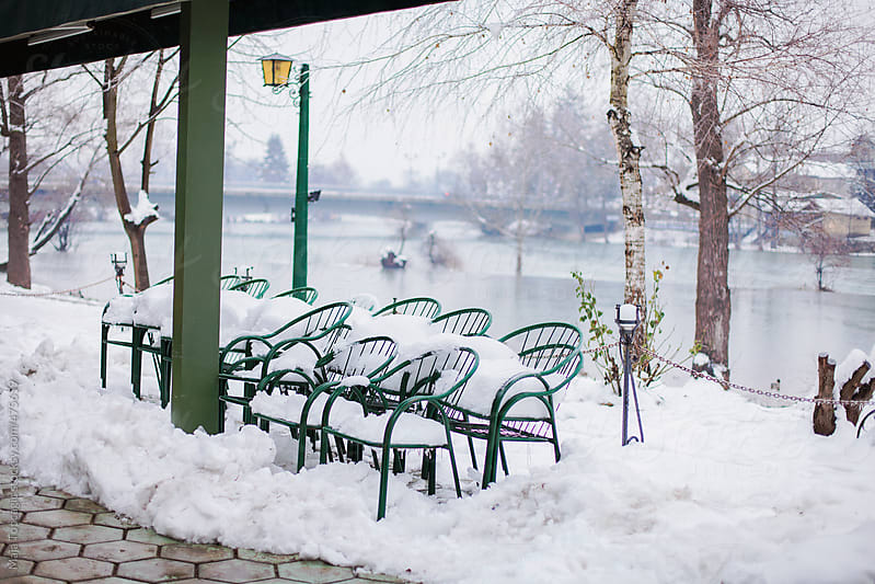 Green chairs covered in snow outside a coffee shop in the city park by Maja Topcagic for Stocksy United