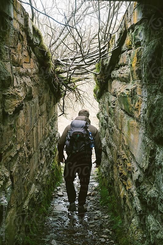 A lone hiker or walker walking through a narrow passage. by Ivo de Bruijn for Stocksy United