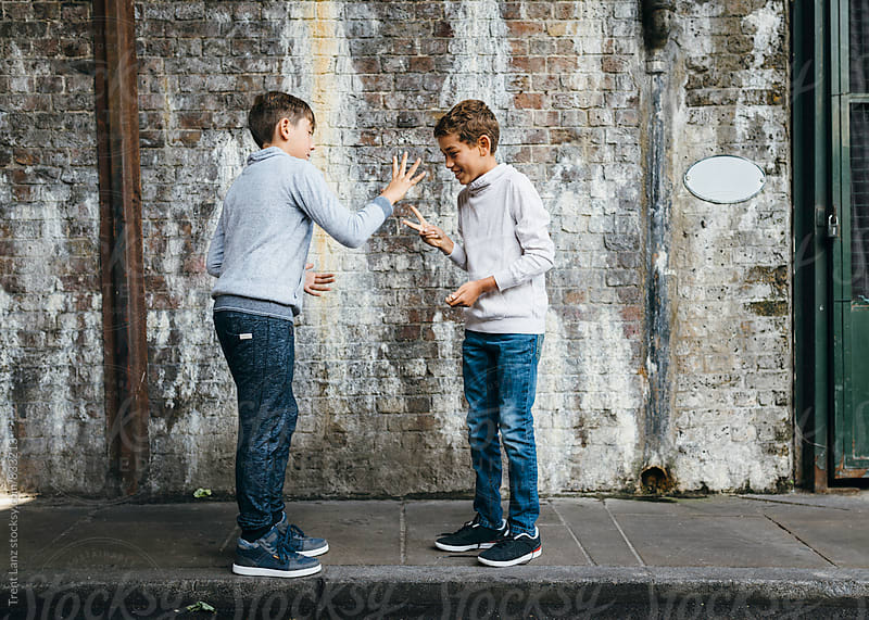 Young handsome boys play on curb in an old tunnel by Trent Lanz for Stocksy United