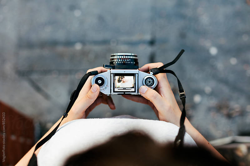 Young woman holding a camera by VegterFoto for Stocksy United