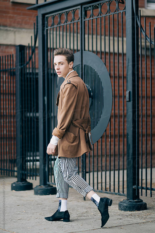 A stylish man walking down the street looking back by Ania Boniecka for Stocksy United