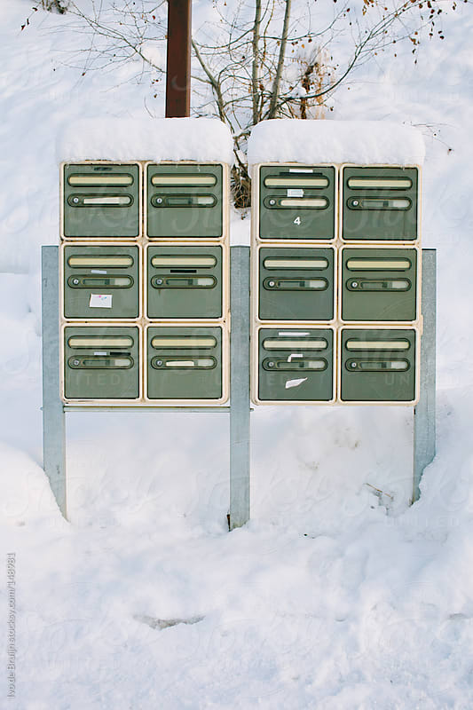A group of mailboxes covered with snow by Ivo de Bruijn for Stocksy United