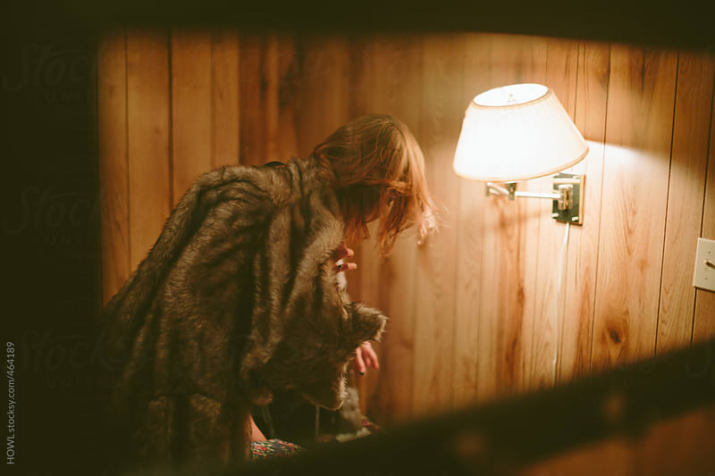 Blonde woman draped in fur, cozy in warm cabin by HOWL for Stocksy United