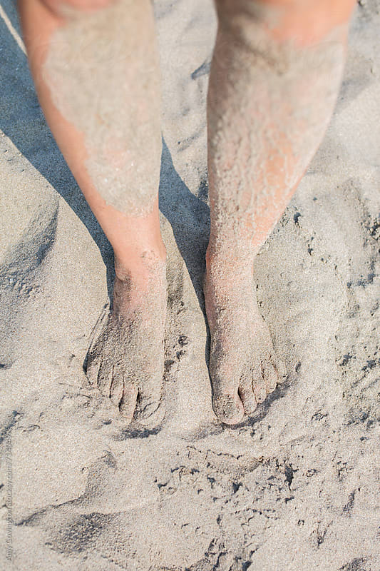 A woman's sandy feet and legs at the beach  by Amy Covington for Stocksy United