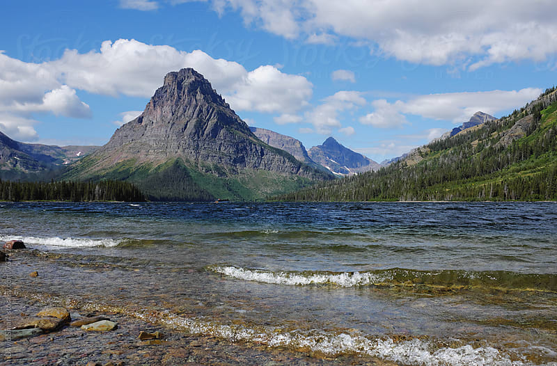 Waves rolling onto the pebbled shore of Two Medicine Lake with Sinopah Mountain dominating the background. by David Smart for Stocksy United