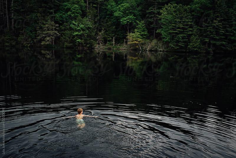 boy swimming in a lake by Léa Jones for Stocksy United