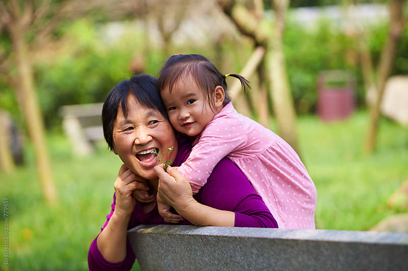 little asian girl with her grandmother outdoor in the park by Bo Bo for Stocksy United